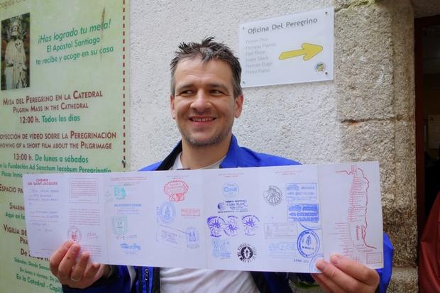 A zarándok iroda előtt Santiagoban a Camino útlevéllel, mindkét oldala tele pecsétekkel :-)